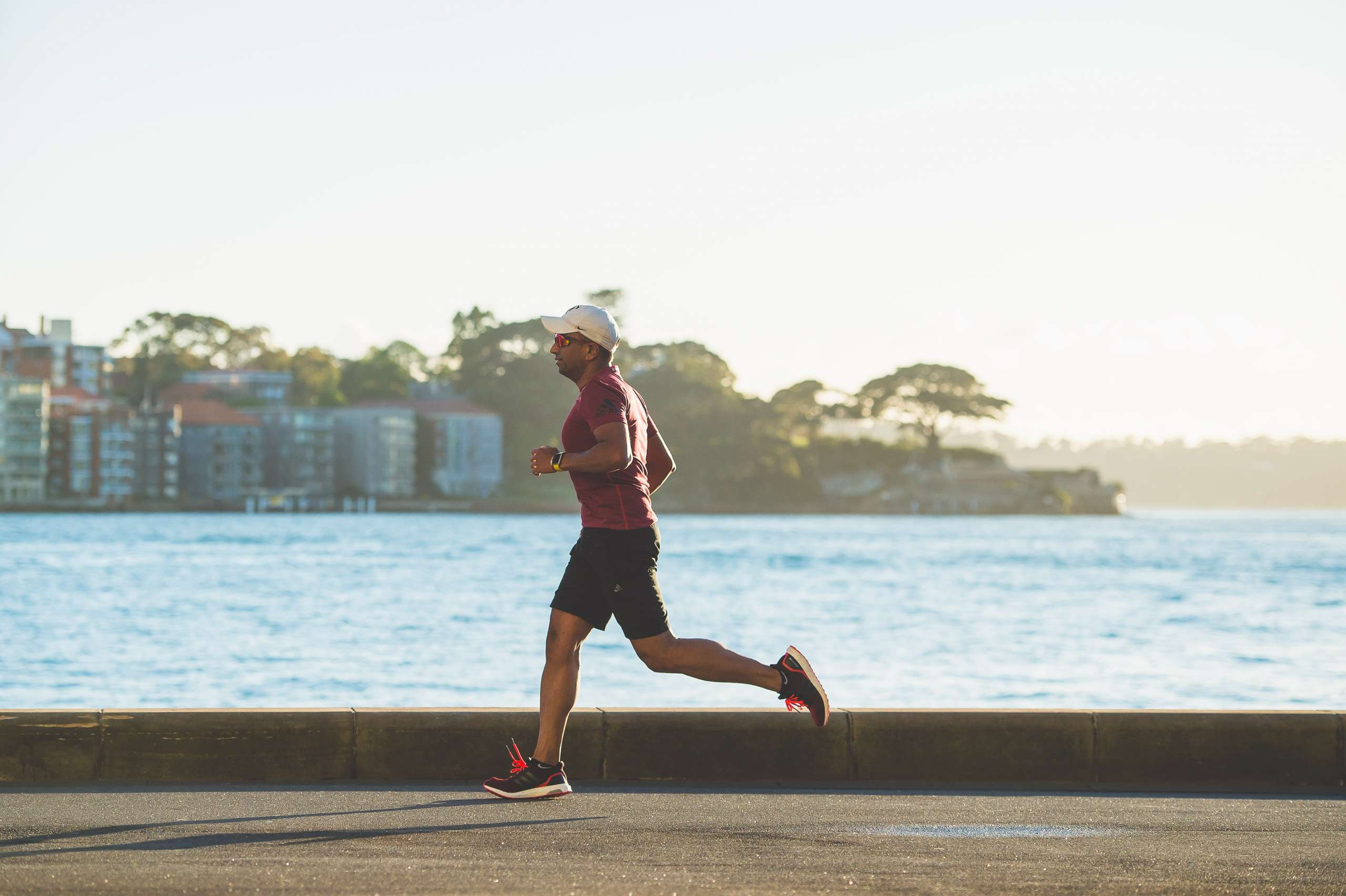 A man runs by a body of water early in the morning.