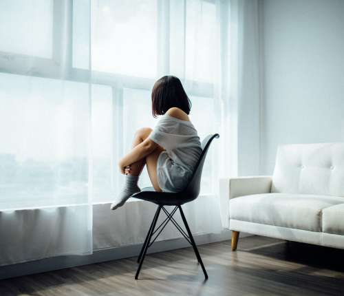 A woman sits alone on a chair in front of a window.