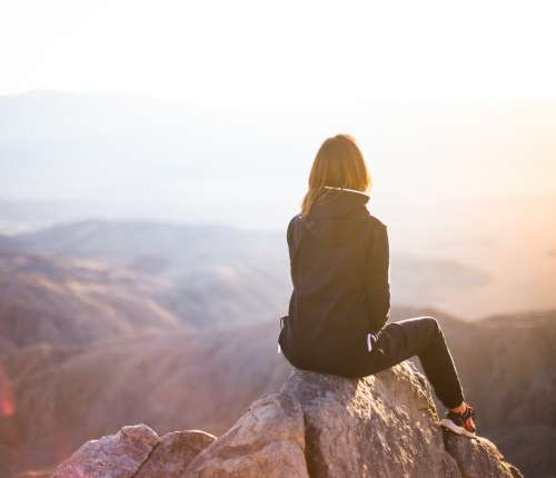A woman sits on a mountain watching the sunset